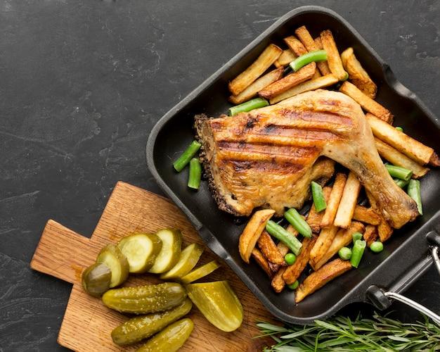 Вид сверху запеченный цыпленок и картофель на сковороде с солеными огурцами