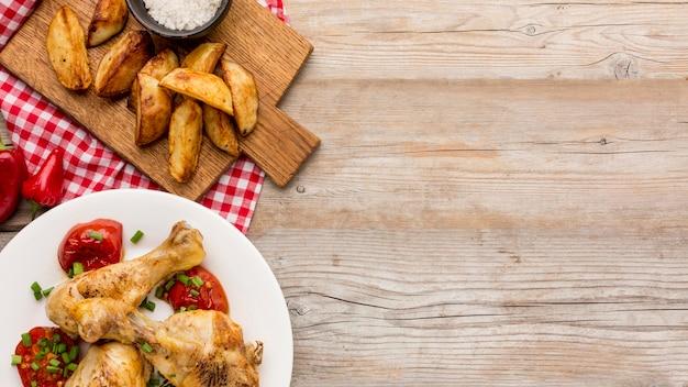 Вид сверху запеченный цыпленок и помидоры на тарелке с дольками и копией пространства