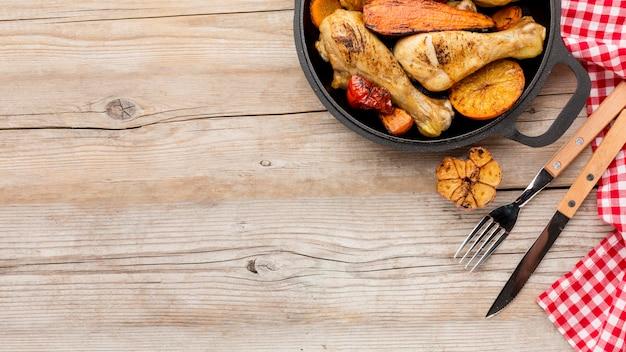 Вид сверху запеченный цыпленок и овощи на сковороде со столовыми приборами и копировальным пространством