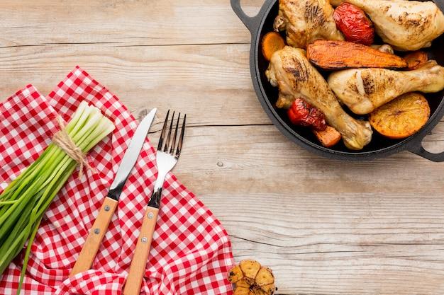 Вид сверху запеченный цыпленок и овощи на сковороде со столовыми приборами