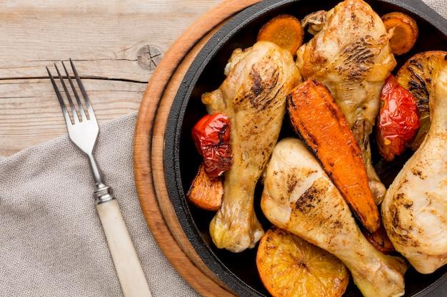 Вид сверху запеченный цыпленок и овощи на сковороде с вилкой