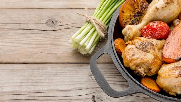 Вид сверху запеченный цыпленок и овощи на сковороде с зеленым луком