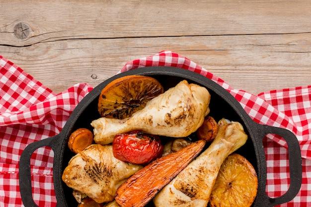 Вид сверху запеченный цыпленок и овощи на сковороде с дольками апельсина
