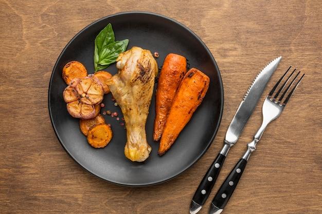 Вид сверху запеченный цыпленок и овощи на тарелке со столовыми приборами