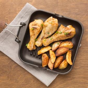 Вид сверху запеченный цыпленок и дольки на сковороде