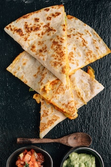 Top view of baked chicken and cheese quesadillas served with salsa and guacamole on stone plate.