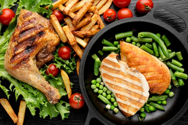Top view baked chicken and cherry tomatoes with fries and peas