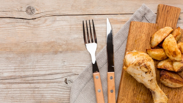 Top view baked chicken drumstick and potatoes on cutting board with cutlery and copy-space