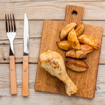 Top view baked chicken drumstick and potatoes on cutting board with cutlery