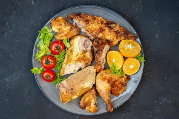 黒いテーブルの上の丸いプレート上の上面図焼きチキンフレッシュトマトレモンスライス