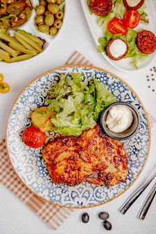 Top view of baked chicken meat with cheese grilled potatoes and tomatoes