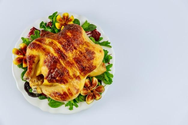 Вид сверху запеченный цыпленок на белой тарелке с салатом и инжиром на белом изолированном фоне.