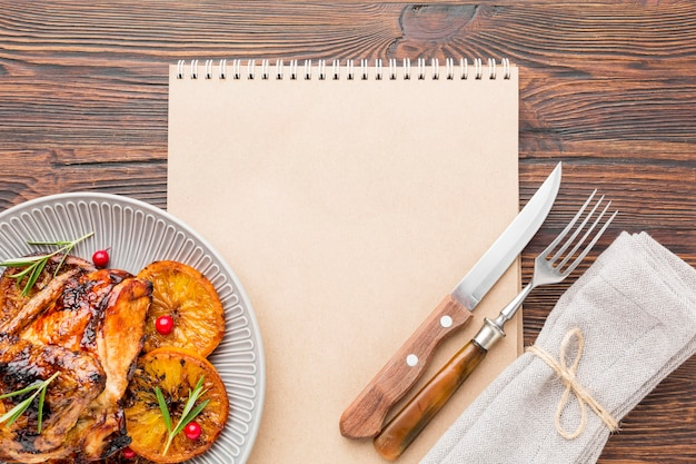 Top view baked chicken and orange slices on plate with cutlery and blank notebook