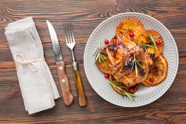 Top view baked chicken and orange slices on plate with cutlery and napkin