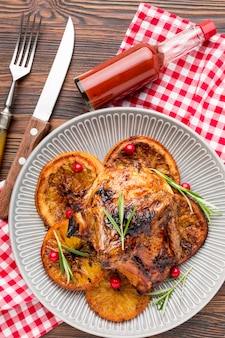 Vista dall'alto di pollo al forno e fette d'arancia sul piatto con posate e salsa