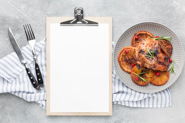 Top view baked chicken and orange slices on plate with kitchen towel and blank notepad