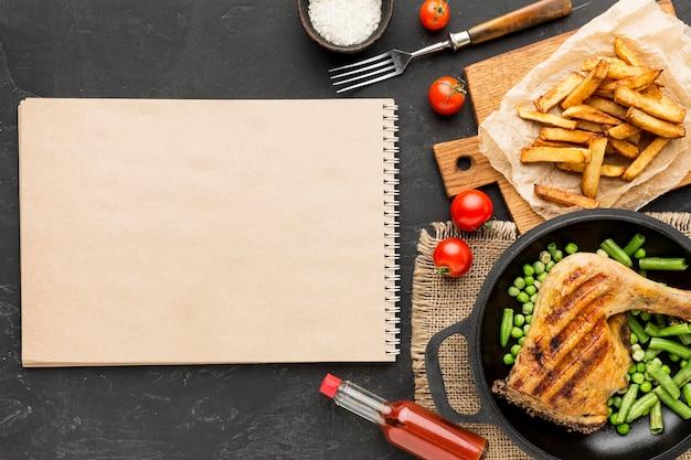 Vista dall'alto pollo al forno e baccelli di piselli in padella con patate e taccuino in bianco
