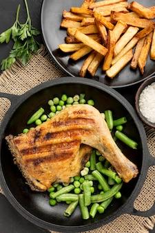 Vista dall'alto pollo al forno e baccelli di piselli in padella con patate