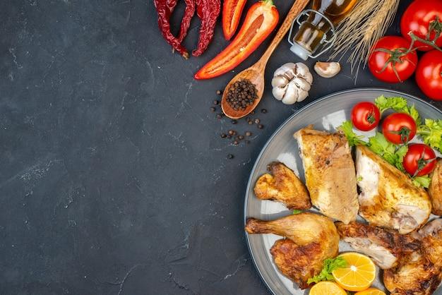 테이블에 검은 후추 마늘 접시에 구운 치킨 토마토 레몬 조각을 상위 뷰
