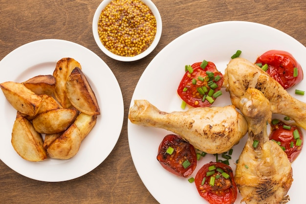 Top view baked chicken and tomatoes on plate with wedges and dijon mustard