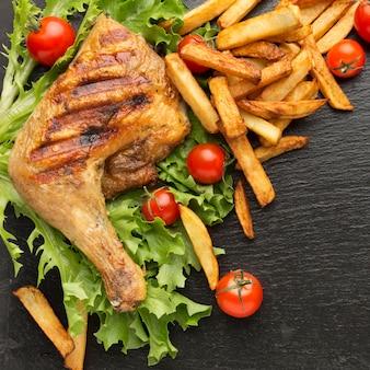 Vista dall'alto di pollo al forno e pomodori con patatine fritte