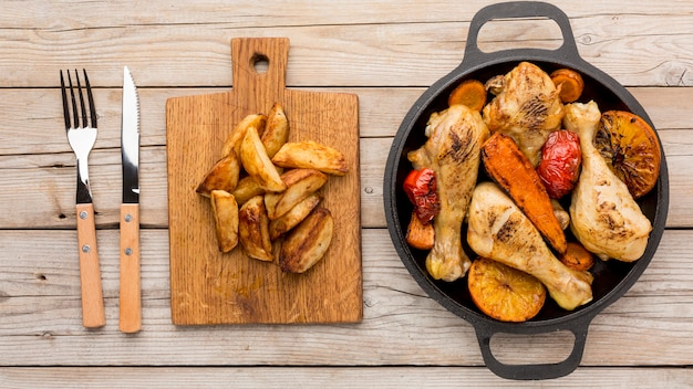 Top view baked chicken and veggies in pan with potatoes and cutlery