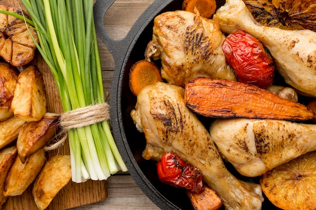 Top view baked chicken and veggies in pan with potatoes and green onions