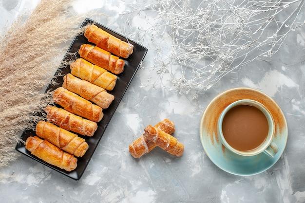 Vista dall'alto di deliziosi braccialetti al forno all'interno della muffa nera con caffè al latte su grigio, biscotto da forno dolce