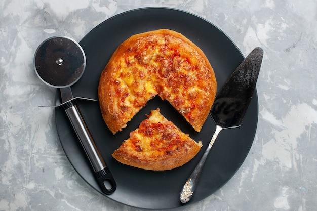 Вид сверху запеченной вкусной пиццы, нарезанной внутри тарелки на белом