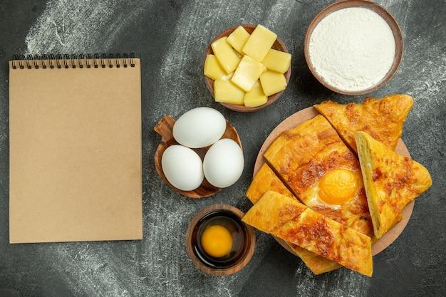 Vista dall'alto di pane all'uovo al forno con uova fresche e formaggio a fette su uno spazio grigio