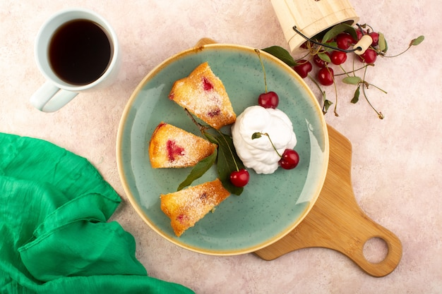 A top view baked fruit cake delicious sliced with red cherries inside and sugar powder inside round green plate with tea on pink