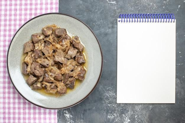 Vista dall'alto fegato e cipolla al forno su piatto ovale su asciugamano da cucina e taccuino vuoto