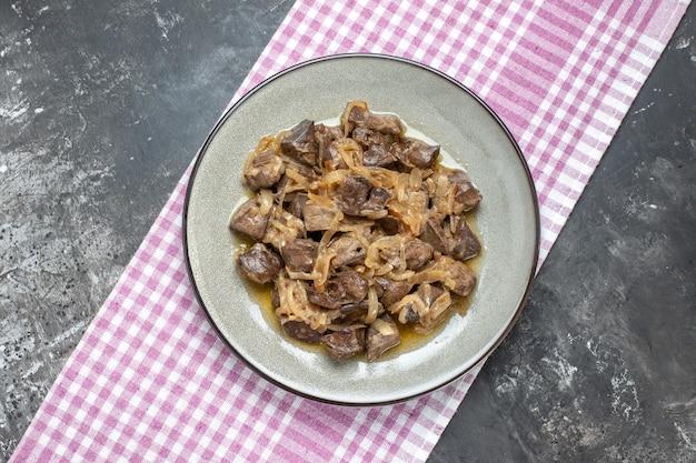 Vista dall'alto fegato e cipolla al forno su piatto ovale su tovaglia