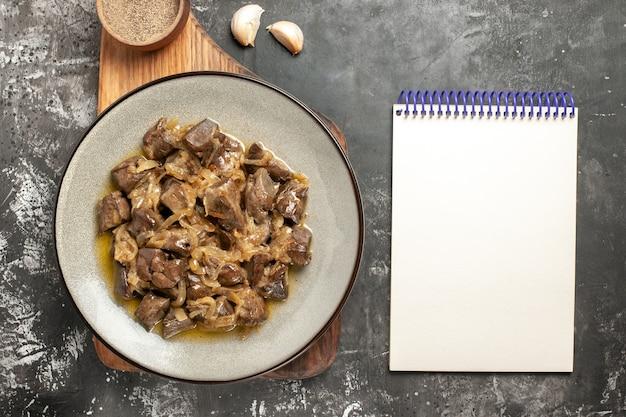 Vista dall'alto fegato e cipolla al forno sul piatto pepe nero sul blocco note dell'aglio del tagliere