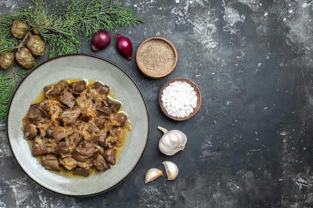 Vista dall'alto fegato e cipolla al forno sul ramo di pino piatto sale e pepe aglio