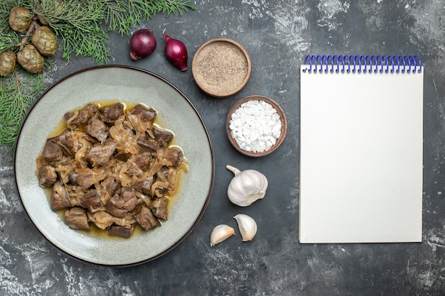 Top view baked liver and onion on plate pine tree branch sea salt and pepper garlic and empty notebook