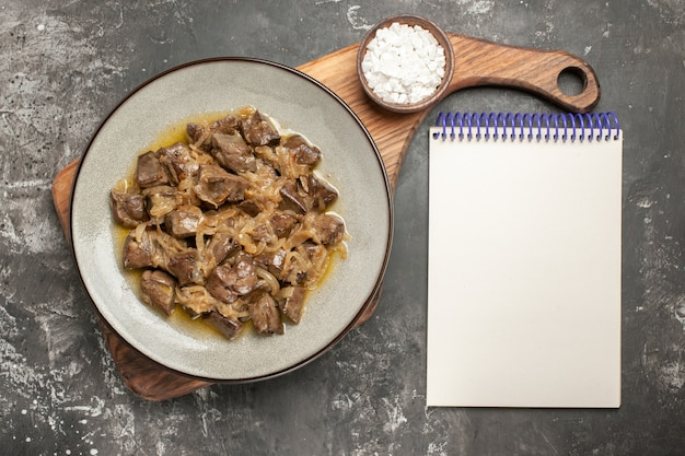 Top view baked liver and onion on plate sea salt on chopping board