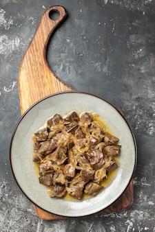 Fegato al forno vista dall'alto con cipolla su piatto rotondo grigio sul tagliere