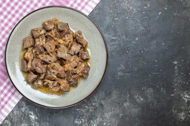 Fegato al forno vista dall'alto con cipolla su piatto rotondo grigio