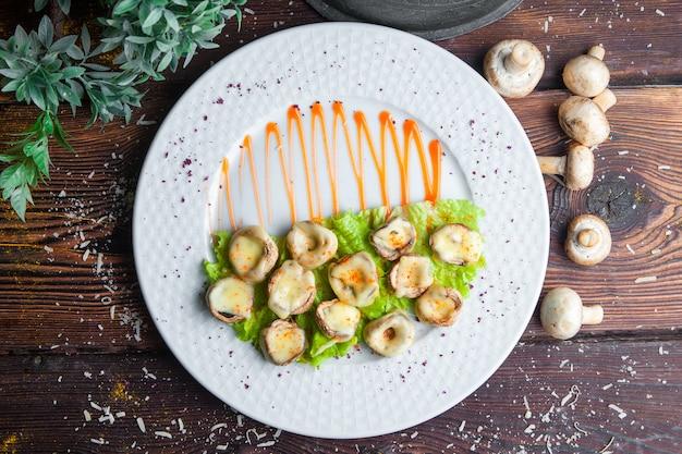 Вид сверху запеченные грибы с сыром и салатом