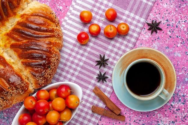 Vista dall'alto pasticceria al forno con prugne alla cannella e tazza di tè sulla scrivania rosa.