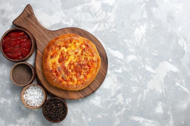 明るい白い机の上にチーズとさまざまな調味料を添えたトップビュー焼きピザ