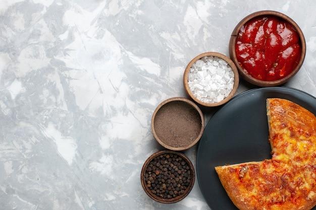 白い机の上にさまざまな調味料で焼いたピザの上面図