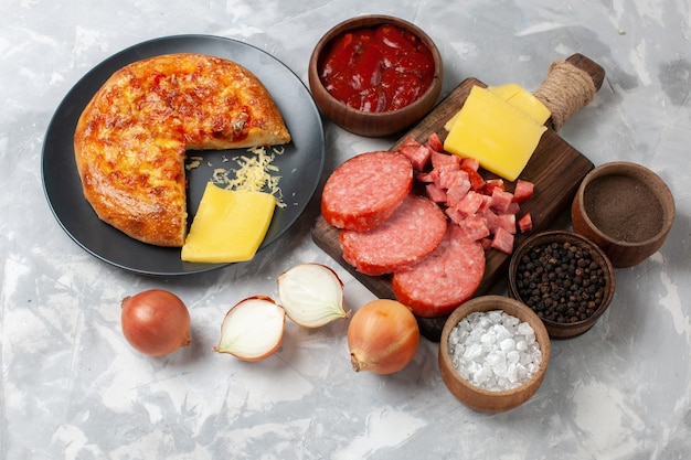 白地に調味料とソーセージを添えたトップビュー焼きピザ
