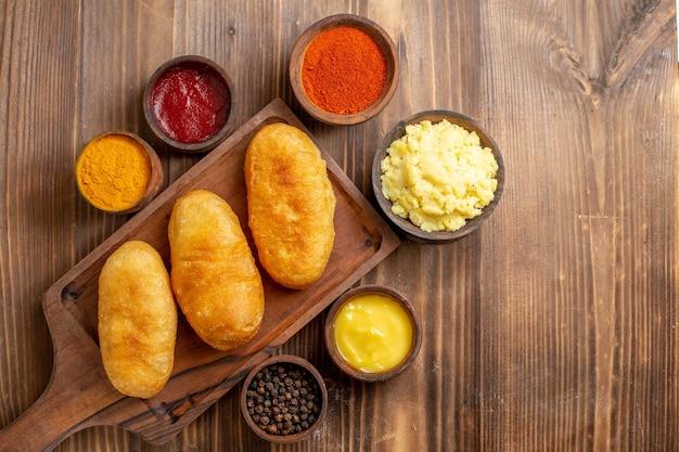 Torte calde di patate al forno vista dall'alto con condimenti su torta da scrivania in legno marrone cuocere la pasta al forno farina di patate