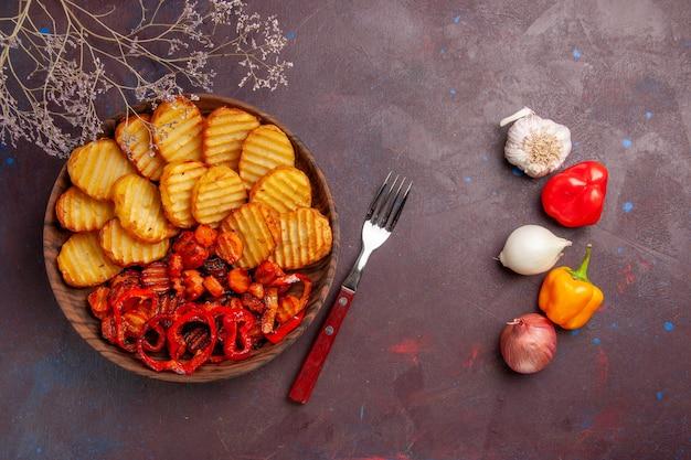 Vista dall'alto di patate al forno con verdure cotte su uno spazio buio