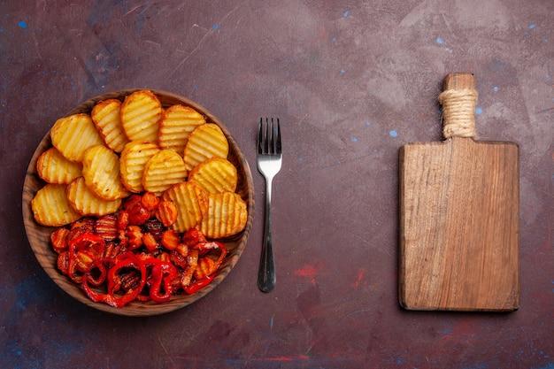 Vista dall'alto di patate al forno con verdure cotte all'interno della piastra sulla scrivania scura