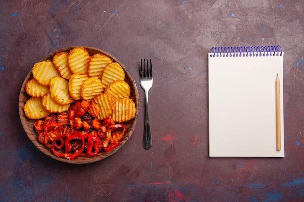 Vista dall'alto di patate al forno con verdure cotte all'interno del piatto nello spazio buio
