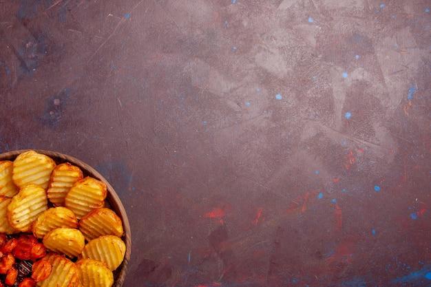 暗い机の上に調理された野菜とベイクドポテトの上面図