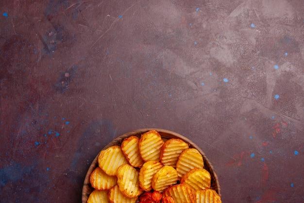 어두운 책상에 조리 된 야채와 함께 구운 감자 상위 뷰